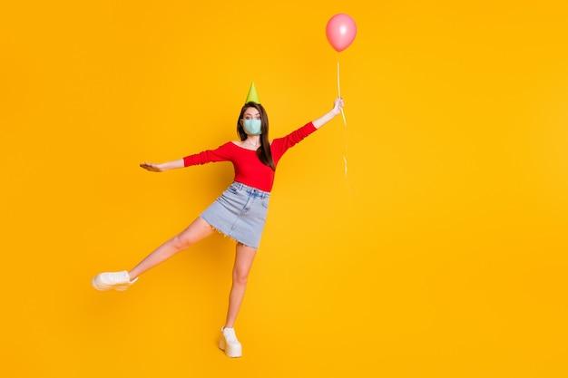 Full size foto meisje medisch masker vasthouden vangen lucht vliegen ballon krijgen verjaardag covid viering slijtage rode top denim jeans korte mini rok benen geïsoleerd heldere glans kleur achtergrond