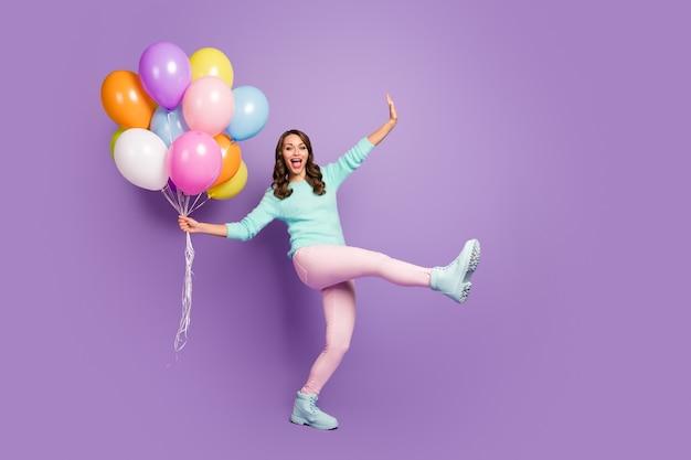 Full-size portret van grappig vrouwelijk meisje geniet van gelegenheid, viert de verjaardag van haar vriend, houdt veel luchtballonnen, schreeuw, draagt pastel zachte trendlaarzen.