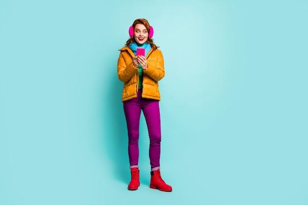Full-size portret van grappige reiziger dame houdt telefoon open mond check nieuwe volgers dragen trendy casual gele overjas sjaal paarse broek schoenen.