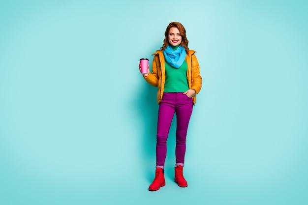 Full size portret van grappige reiziger dame houdt warme koffie drank lopen straat dragen casual gele overjas sjaal paarse broek coltrui schoenen.