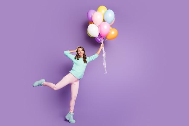 Full size portret van verrast vrouwelijk meisje krijgt aanwezig veel ballonnen vliegen lucht ze vangen onder de indruk schreeuw wow omg draag roze broek broek pastel turquoise trui.