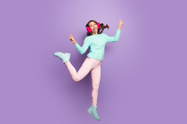 Full size portret van vrolijk meisje springen genieten van vrije tijd maken v-sign dwaas toon tong uit dragen wintertaling turkoois fuzzy zachte pullover pastel roze broek broek.
