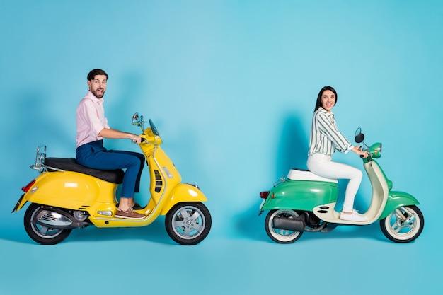 Full size profiel zijfoto gek geschokt vrouw man rijder motorrijders rijden motor fiets onder de indruk ongelooflijke uitstapje uitzicht dragen formalwear broek broek geïsoleerd blauwe kleur muur