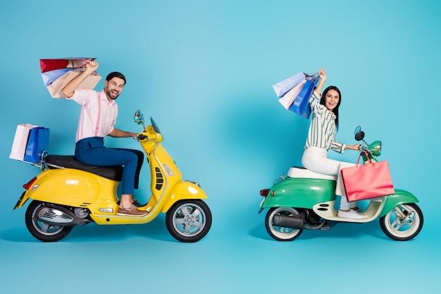 Full size profiel zijfoto twee personen echtgenote man bestuurder motorrijder rijden motorfiets vervoer winkel winkelcentrum veel tassen gekocht slijtage formalwear overhemd broek broek geïsoleerde blauwe kleur muur