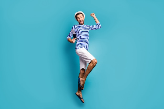 Full size profielfoto van funky gekke kerel toerist spring hoog vakantie vieren start eindelijk visum dragen gestreepte matroos shirt vest pet korte broek flip flops geïsoleerde blauwe kleur
