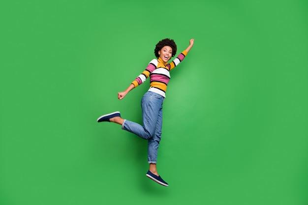 Full size profielfoto van grappig funky afro amerikaans meisje superheld concept sprong vliegen motivatie stretch armen vuist bereiken korting dragen heldere glans outfit