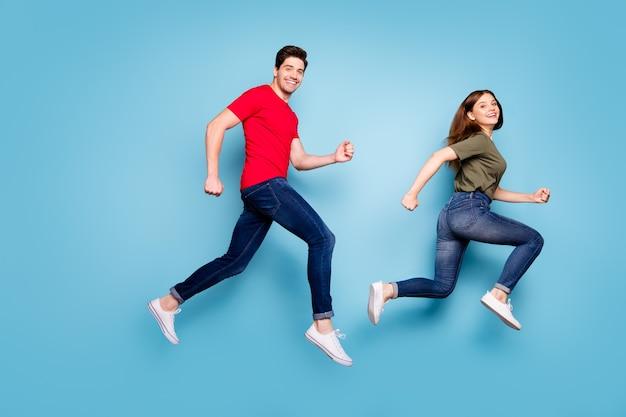 Full size profielfoto van vrolijke romantische getrouwde mensen springen rennen na lente kortingen dragen groen rood t-shirt denim jeans sneakers geïsoleerd op blauwe kleur achtergrond