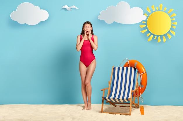 Full size shot van onder de indruk geschokte vrouw in zwembroek, houdt handen op de wangen en mond opent, heeft een badplaats