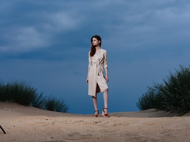 Fulllength portret van een vrouw in een zomerjurk en rode sandalen op het zand op het strand