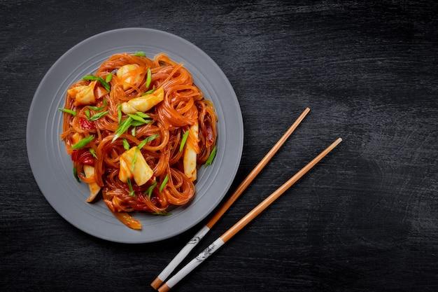 Funchoza met inktvis en groenten op een zwarte achtergrond, bovenaanzicht, kopie ruimte. glasnoedels, aziatisch eten.