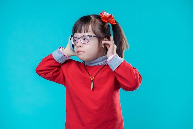 Functies gebruiken. druk mooi kind dat doet alsof ze op haar mobiele telefoon praat terwijl ze tegen de blauwe muur staat en haar oor aanraakt