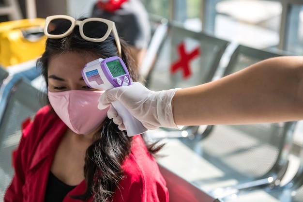 Functionaris van de luchthaven met handschoen controleert de temperatuur van de passagier door een infraroodthermometer op de terminalstoel