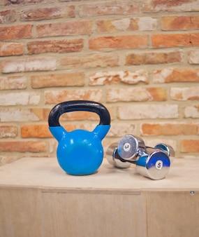 Functioneel trainingsconcept. kettlebell, halter staan op houten kist tegen de bakstenen muur. functioneel trainingsconcept. gratis krachttraining. trainingsapparatuur