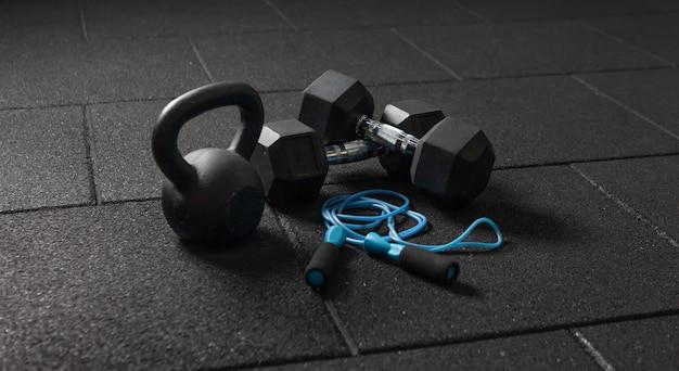 Functionele training sportuitrusting. kettlebell en springtouw, halters op een donkere zwarte vloer. bodybuilding en fitness