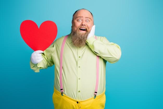 Funky dikke man houdt rood valentijn papieren kaart hart op blauwe achtergrond