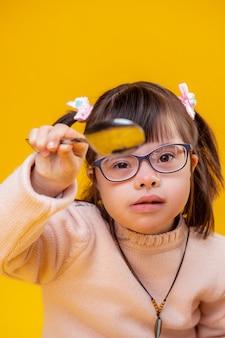 Funky donker kapsel. buitengewoon klein kind met gezichtskenmerken die een heldere bril dragen en met een metalen lepel spelen