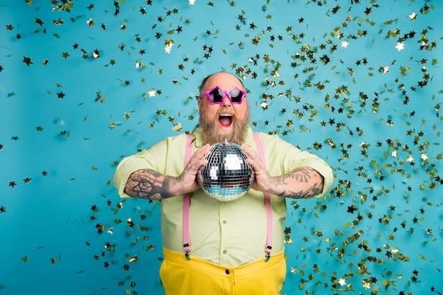 Funky kerel houdt discobal met plezier op blauwe achtergrond met vallende confetti
