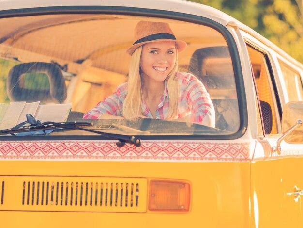 Funky meisje in retro auto. gelukkige jonge vrouw die lacht naar de camera terwijl ze door het raam van het voertuig kijkt