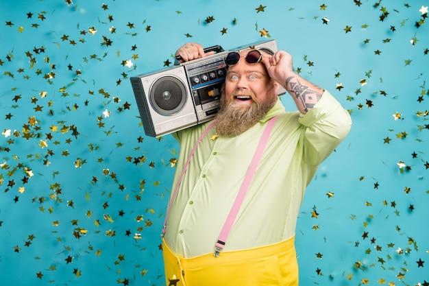 Funky overgewicht man met boombox op blauwe achtergrond met vallende confetti