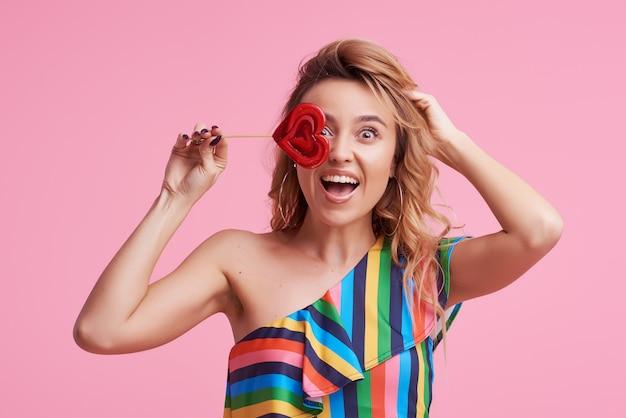 Funky positieve vrolijke aantrekkelijke dame met haar stijlvolle trendy golvende krullende haar, houdt een sukkel op stok geïsoleerd op roze
