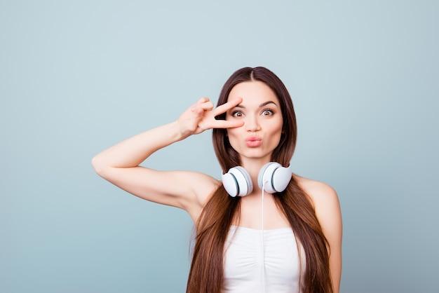 Funky sfeer! jonge aantrekkelijke brunette model is gek rond met pruilende lippen, twee vingers ondertekenen, koptelefoon in zomer outfit, op pure lichtblauwe ruimte
