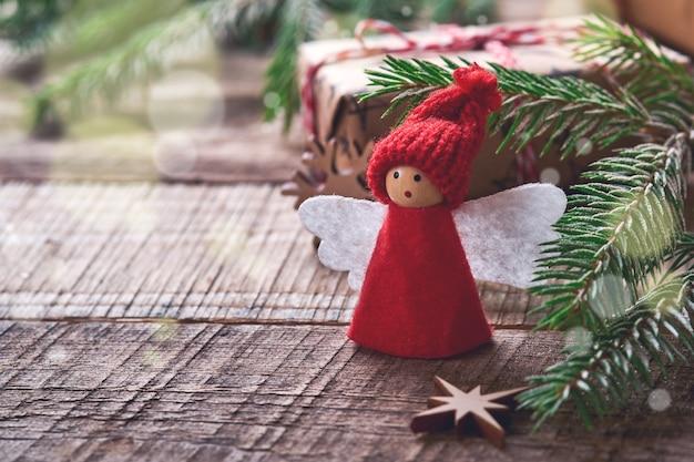 Funny christmas angel fir boomtakken en geschenkdozen op winter besneeuwde achtergrond met besneeuwde takken. kerst of winter concept.