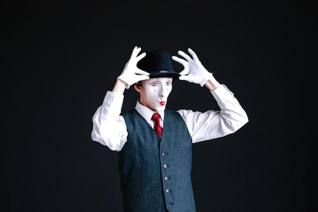 Funny mime fixeert zijn hoed