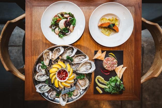 Fusie fine dining maaltijd: veel soorten verse oesters, ravioli in roomsaus met gegrilde zalm