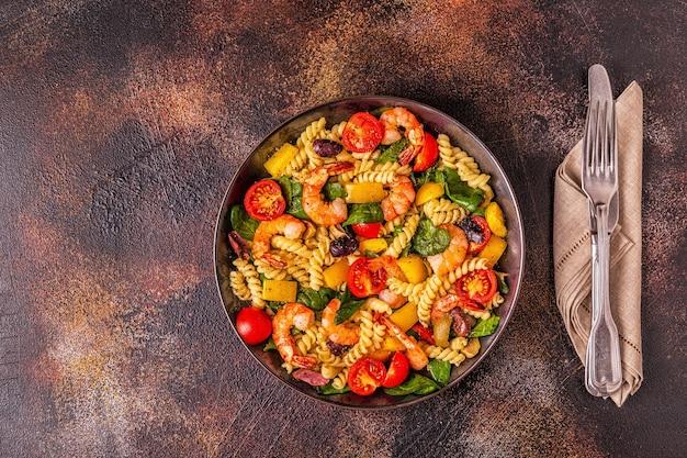 Fusili pastasalade met garnalen, tomaten, paprika, spinazie, olijven, bovenaanzicht.