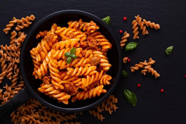 Fusilli-deegwaren met bolognese sausen in de zwarte ijzerpan