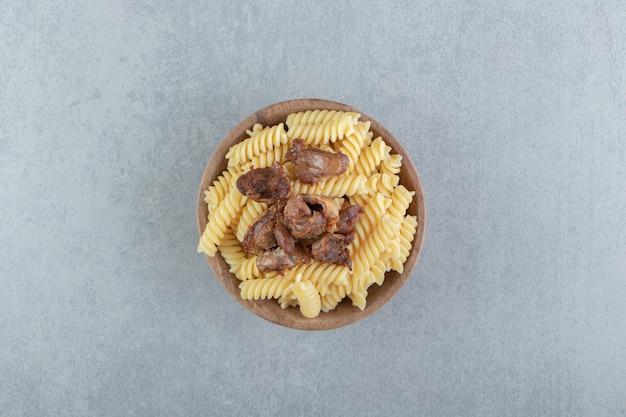 Fusilli en gebakken kip in houten kom.