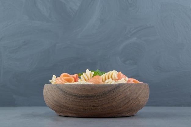 Fusilli en zeeschelppasta in houten kom