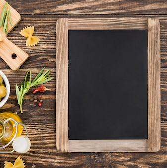 Fusilli met olijven en groenten naast schoolbord