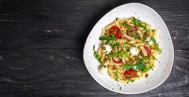 Fusilli pasta caprese salade met kerstomaatjes en mozzarella kaas op zwarte houten tafel. lang bannerformaat, bovenaanzicht.