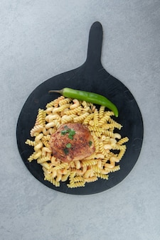 Fusilli pasta, chili peper en kip op zwart bord.