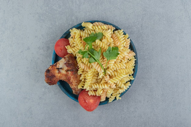 Fusilli pasta en kippenvleugel op blauw bord.