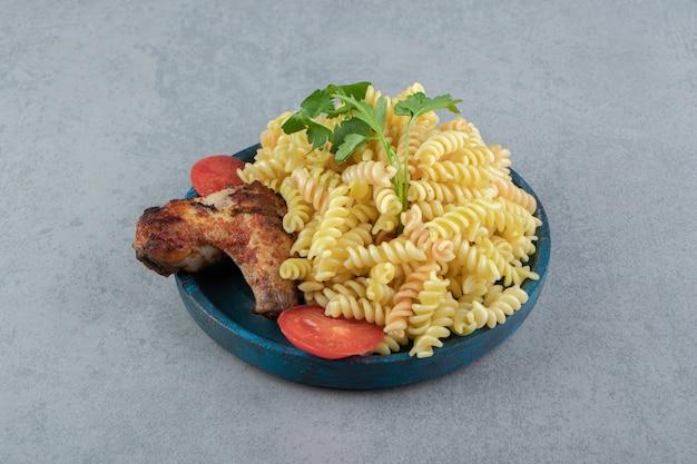 Fusilli pasta en kippenvleugel op blauw bord