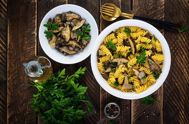 Fusilli pasta glutenvrij met bospaddestoelen op een witte plaat. vegetarisch / veganistisch eten. italiaanse keuken. bovenaanzicht, plat leggen, kopie ruimte
