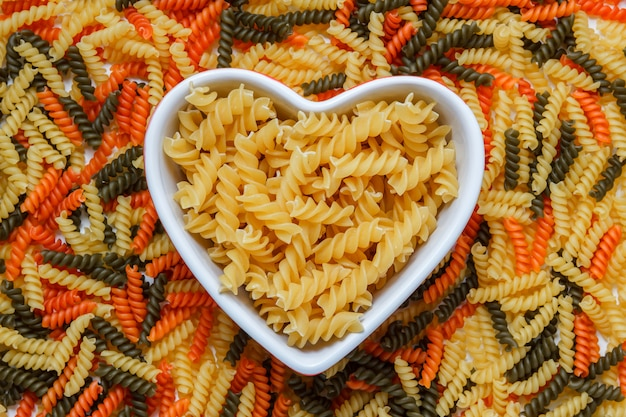 Fusilli pasta in een hartvormige kom op macaroni tafel, plat lag.