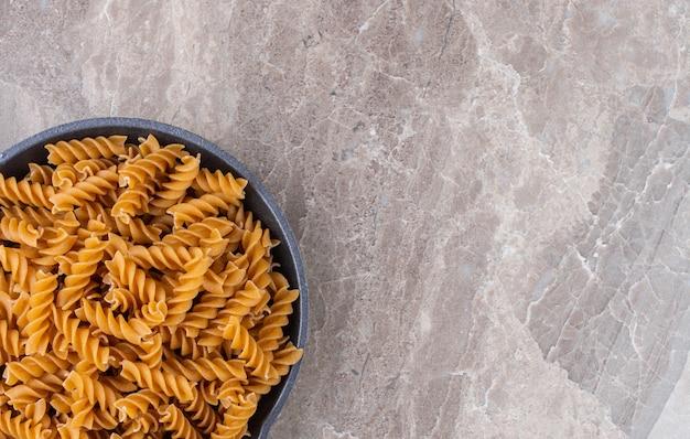 Fusilli-pasta in een pan, op het marmer.