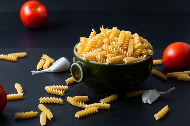 Fusilli pasta in groene keramische kom met ingrediënten