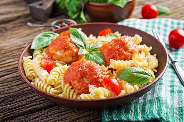 Fusilli pasta met gehaktballetjes in tomatensaus en basilicum in kom