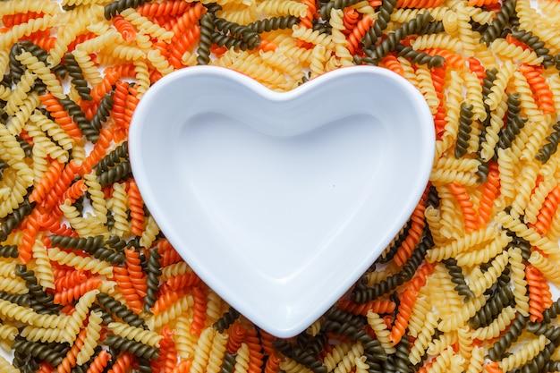 Fusilli pasta met hartvormige kom plat leggen.