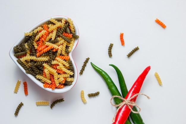 Fusilli pasta met hete pepers in een kom op witte tafel, bovenaanzicht.