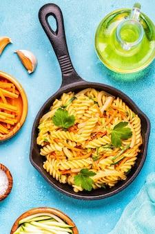Fusilli pasta met inktvis, courgette en wortelen, bovenaanzicht.
