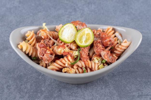 Fusilli pasta met kip in keramische kom.