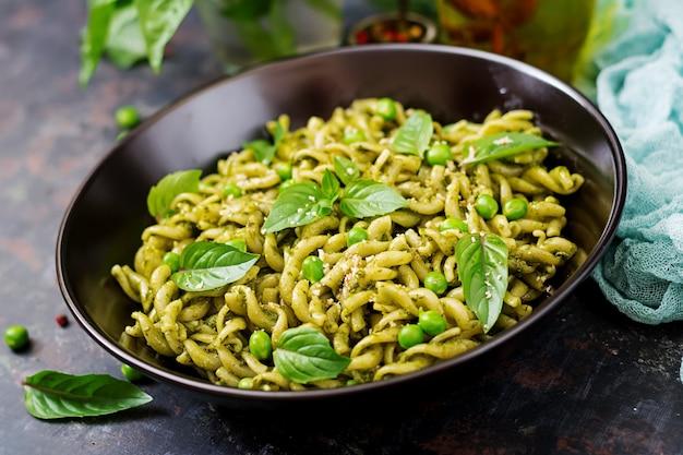 Fusilli pasta met pestosaus, doperwtjes en basilicum.