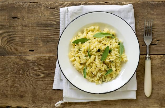 Fusilli pasta met salie bladeren in een witte kom