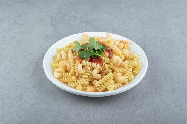 Fusilli pasta met saus op witte plaat.