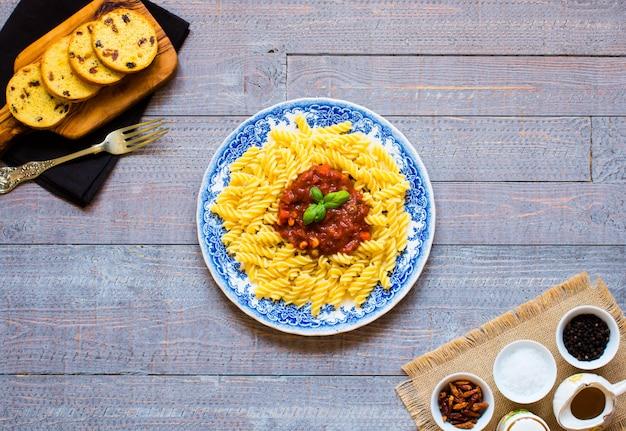 Fusilli pasta met tomatensaus, tomaten, ui, knoflook, gedroogde paprika, olijven, peper en olijfolie op een houten tafel